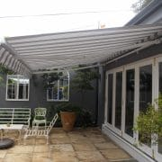 It is an awning that fits against the wall and opens out with 2 arms that are covered with canvas material. They can be operated either manually or motorised. They are not waterproof but are designed to provide shade. They need to be retracted in windy conditions.